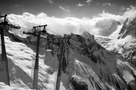 ropeway: Black and white view on cable car at ski resort and mountains in sunlight clouds. Caucasus Mountains, region Dombay. Stock Photo
