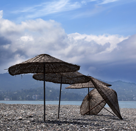 felled: Old sunshade on deserted beach out of season in sun day Stock Photo