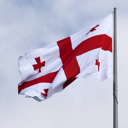 Flag of Georgia and gray sky with clouds at windy day. Close-up view. Stock Photo