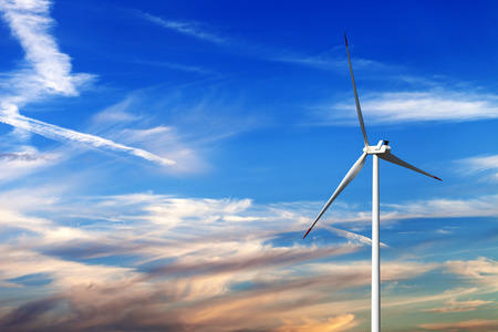 Wind turbine and multicolor sunrise sky with clouds at windy day Stock Photo