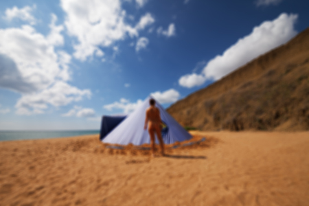 Blurred view of conical tent and sunbathing girl on summer beach with cloudy blue sky. Use as background.