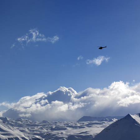 Helicopter above snowy plateau and sunny sky in winter evening. Caucasus Mountains, Georgia, region Gudauri. Stock Photo