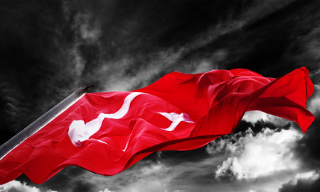 Flag of Turkey waving against black and white sky with dark storm clouds Stock Photo