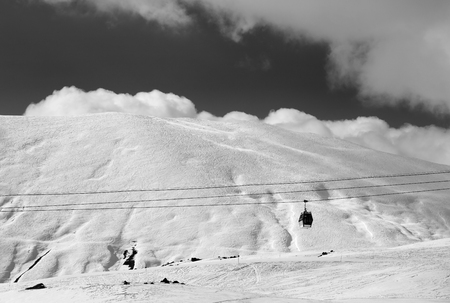 winter road: Black and white view of gondola lift and off-piste slope at evening. Caucasus Mountains, Georgia, region Gudauri. Stock Photo