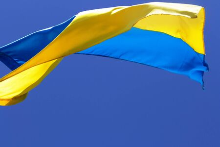 Flag of Ukraine waving in wind on clear blue sky at sun day Stock Photo