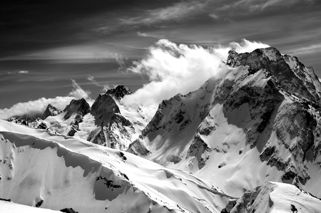 Black and white winter mountains with snow cornice and cloudy sky in nice sun day. Caucasus Mountains, region Dombay. Mount Dombai-Ulgen. View from the top of Musa Achitara.