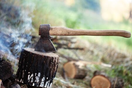 Axe in tree stump and smoke from campfire in morning at summer forest