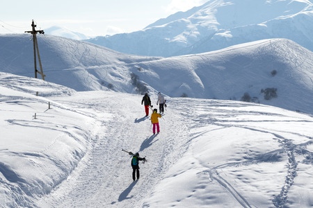 off piste: Skiers and snowboarders on snow road at sun winter morning. Caucasus Mountains, Georgia, region Gudauri. Editorial