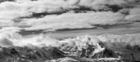 Black and white panoramic view on snow mountains and sunlight cloudy sky at winter evening. Caucasus Mountains. Svaneti region of Georgia.