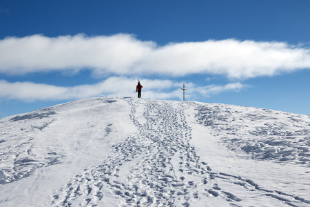 Skier with skis on his shoulder go up to top of mountain in nice sun day. Caucasus Mountains in winter, Georgia, region Gudauri, Mount Kudebi. Stock Photo