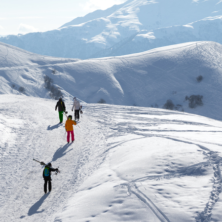 Skiers and snowboarders go up on snowy road at sun winter morning. Caucasus Mountains, Georgia, region Gudauri.