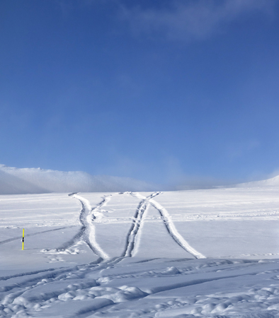 Off-piste ski slope with new-fallen snow and traces from ski, snowboard after snowfall. Caucasus Mountains in sun winter evening, Georgia, region Gudauri Stock Photo