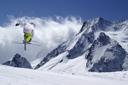 Freestyle ski jumper with crossed skis in high snowy mountains