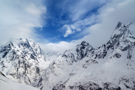 Gray high mountain peaks covered with ice and beautiful blue sky with clouds at winter day after snow storm. Caucasus Mountains, region Dombay.