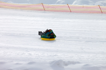 Snow tubing on ski resort at sun winter day in snowy mountains