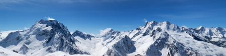 Panoramic view of snow-capped mountain peaks with mount Dombay-Ulgen and beautiful blue sky with clouds at sun windy day. Caucasus Mountains in winter, region Dombay.