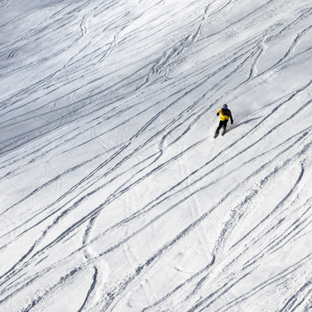 Skier downhill on snowy ski slope for freeride at sun winter day after snowfall