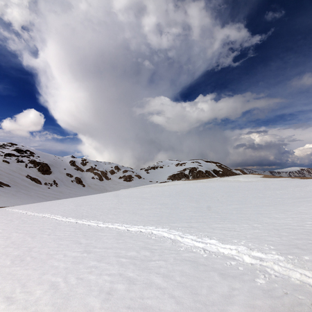 Snowy mountains with footpath and sky with clouds. Turkey, Central Taurus Mountains, Aladaglar (Anti-Taurus) view from plateau Edigel (Yedi Goller).