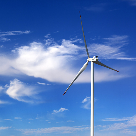 Wind turbine and blue sky with clouds at sun windy day Archivio Fotografico
