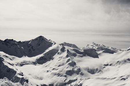 Black and white snowy mountains at winter evening. Caucasus Mountains. View from mount Elbrus. Stock Photo