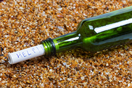Bottle of wine with help message driven ashore on wet sand beach at sun summer day
