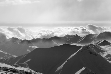 Silhouette of evening sunlight snowy mountains in mist. Caucasus Mountains, Georgia, region Gudauri at winter. Black and white toned landscape. Imagens