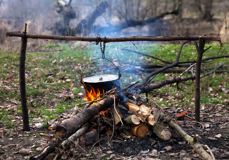 Cooking in old sooty cauldron on campfire at forest