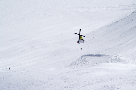 Skier jumping in snow park at ski resort on sun winter day