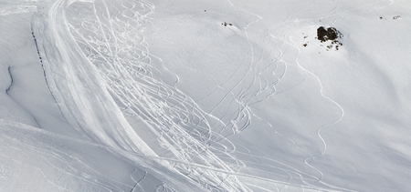 Panoramic view on snowy off-piste slope with traces of skis and snowboards. Caucasus Mountains in sun winter day, Georgia, region Gudauri. 免版税图像