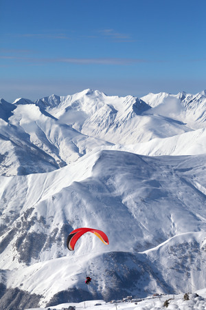 Paragliding at snowy mountains over ski resort at sunny cold day. Caucasus Mountains in winter. Georgia, region Gudauri.