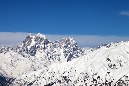 Snowy mountains and blue sky with clouds at sunny winter day. Caucasus Mountains. Svaneti region of Georgia, Mounts Ushba and Chatyn. Stock Photo