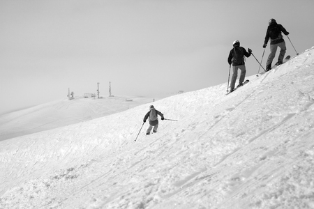 Skiers descent on snowy freeride slope and overcast misty sky at day with bad weather before blizzard. Caucasus Mountains in winter, Georgia, region Gudauri. Black and white toned landscape.