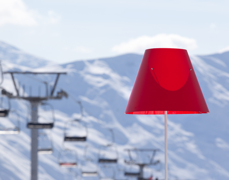 Lamp with red lampshade in outdoor cafe at ski resort, snowy winter mountains and chair-lift in background. Caucasus Mountains. Georgia, region Gudauri.