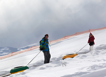 Happy father and daughter with snow tube in snowy sunlight mountains with gray cloudy sky. Caucasus Mountains, Georgia, region Gudauri at winter.