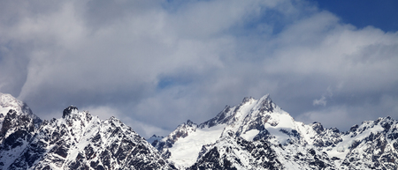Panoramic view on snowy rock mountains in clouds at sun winter day. Caucasus Mountains. Svaneti region of Georgia.
