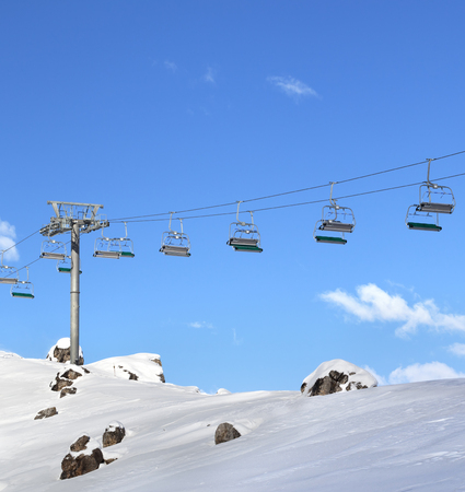 Sunlight chair-lift and blue sky with clouds at ski resort on sunny day. Caucasus Mountains in winter, Shahdagh, Azerbaijan.