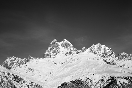 Black and white snowy mountains at sunny winter day. Caucasus Mountains. Svaneti region of Georgia, Mounts Ushba and Chatyn. Stock Photo