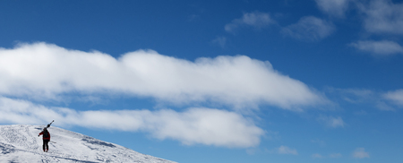 Blue sky and skier with skis on his shoulder go up to top of mountain. Caucasus Mountains in winter, Georgia, region Gudauri, Mount Kudebi. Panoramic view. Stock Photo
