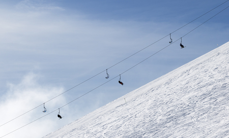 Snowy off-piste ski slope with traces from skis and snowboards and chair-lift against sky with clouds in winter