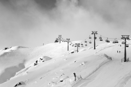 Snowy ski slope and ski-lift at ski resort at sunny winter evening. Caucasus Mountains, Shahdagh, Azerbaijan. Black and white toned landscape. 写真素材