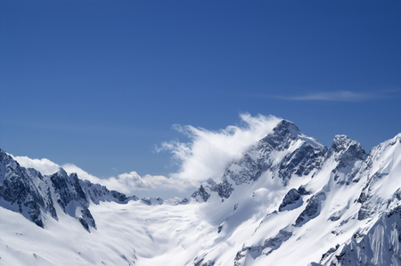 Winter snowy mountains in clouds and beautiful blue sky at windy day. Caucasus Mountains, region Dombay.