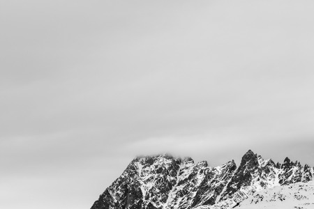 Rocky mountains in snow and overcast gray sky at winter day. Caucasus Mountains, Svaneti region of Georgia. Black and white toned landscape. Stock Photo
