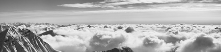 Large panorama of snowy mountains covered with beautiful sunlight clouds at sunny winter evening. Caucasus Mountains, Georgia, region Gudauri. Black and white toned landscape.