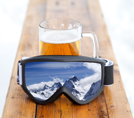 Ski goggles with reflection of winter snowy mountains and glass mug with fresh cold beer on wooden bench in outdoor cafe at ski resort Stock fotó