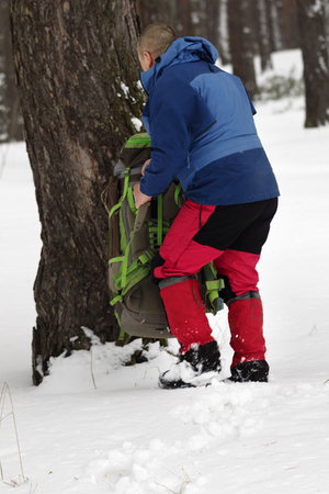 Hiker takes his backpack in snowy pine forest at winter. Remote location.