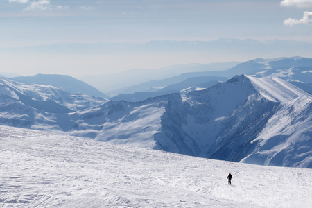 Silhouette of skier on snowy off-piste slope and mountains in haze at sunny winter morning. Caucasus Mountains, Georgia, region Gudauri.