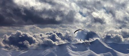 Vista panorámica de la montaña nevada de noche con nubes y silueta de paracaidista. Montañas del Cáucaso. Georgia, región de Gudauri en invierno.