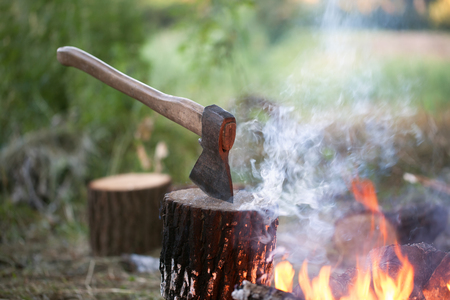 Axe in tree stump and campfire with smoke in summer forest at evening Stock Photo