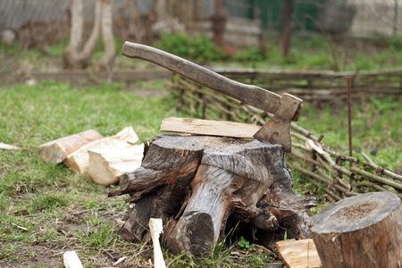 Old axe in tree stump on cottage glade at summer day Stock Photo