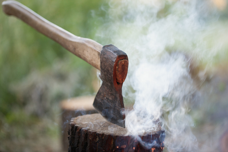 Axe in tree stump and smoke from campfire